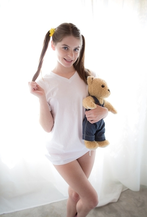 Innocent teenage enters the room with Teddy in hands and puts it aside to strip