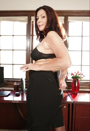 Elegant middle-aged business lady unclothes and poses in the office